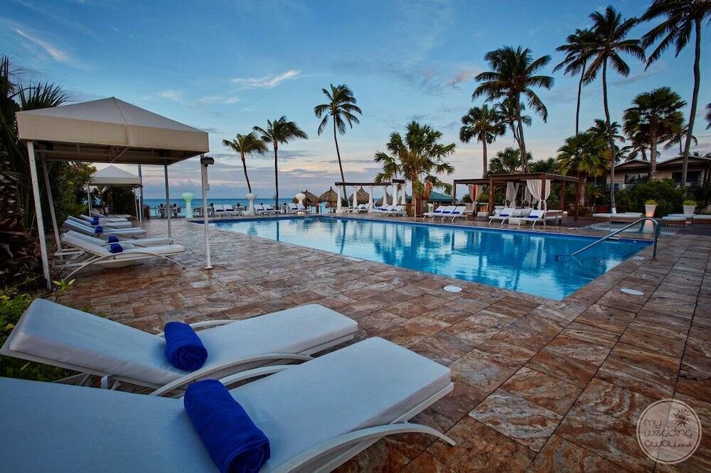 Pool with marble tiles lounge chairs and palm trees in the background
