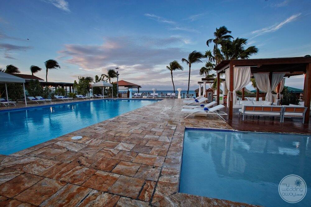 Pool and hot tub with cabana lounge chairs and ocean in the background