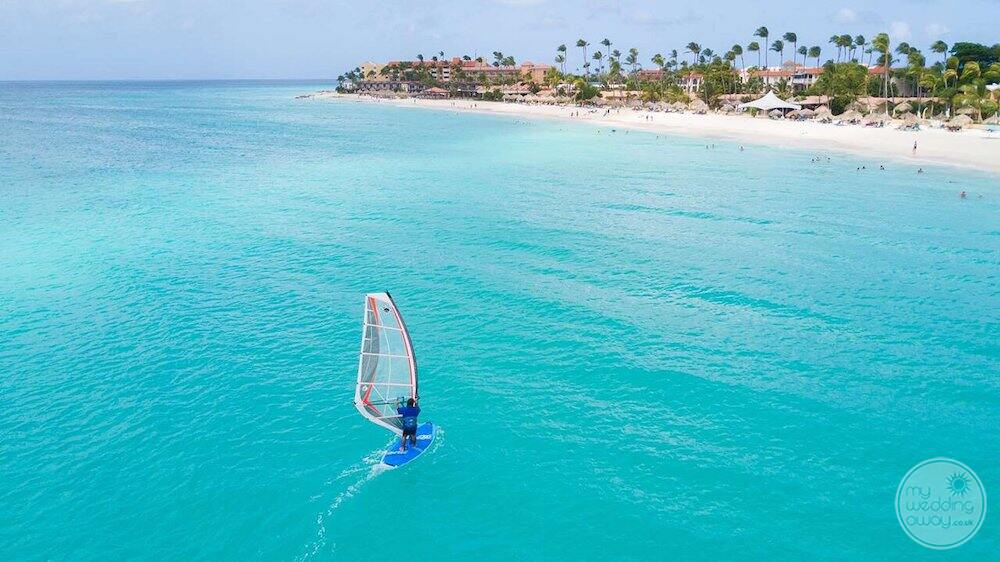 Aerial view of resort guest wind surfing in the ocean with beach in the background