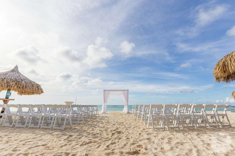 set up of waiting chairs and gazebo on the beach for a ceremony in the afternoon