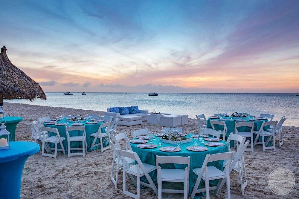 evening reception table and chairs set up on the beach with the lounge area at sunset