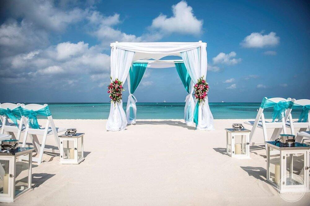 gazebo on the beach with chairs set up in blue and white material