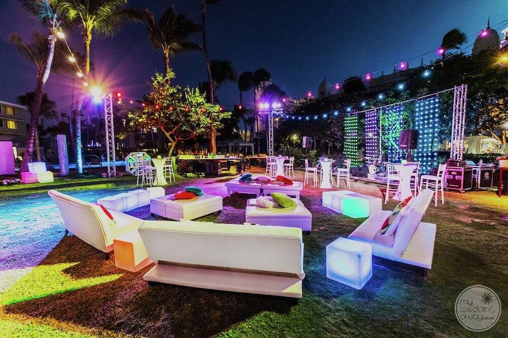 lounge style chairs and couches set out by the pool for an evening wedding reception