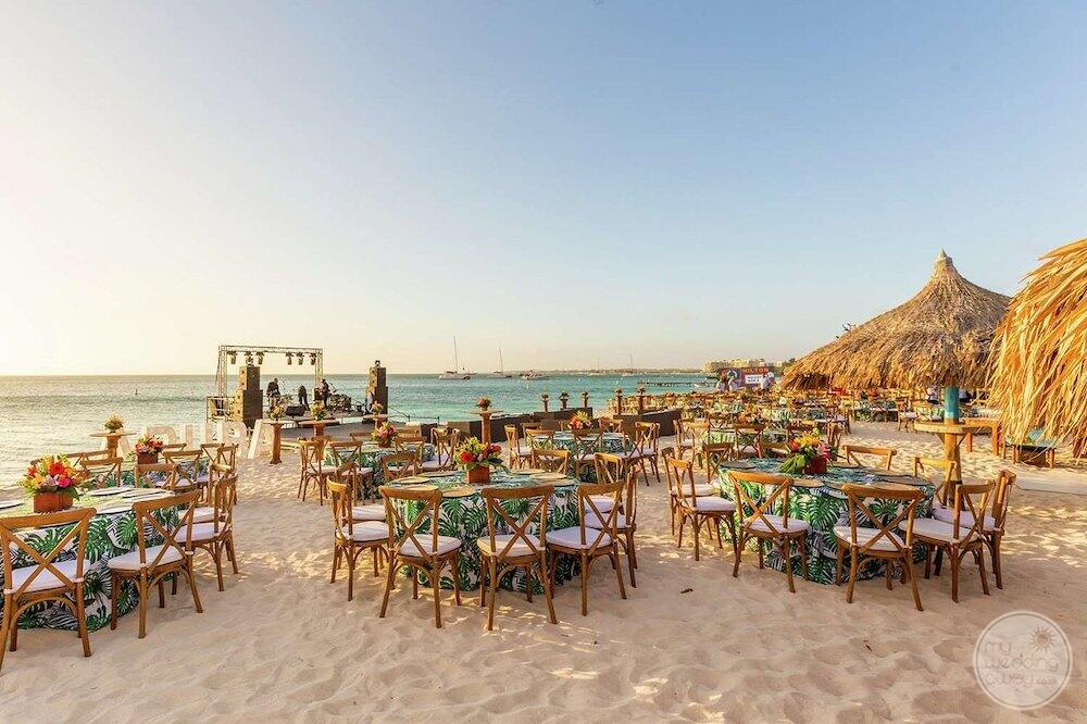 reception set up on the beach with tropical theme tablecloth and DJ beside the ocean