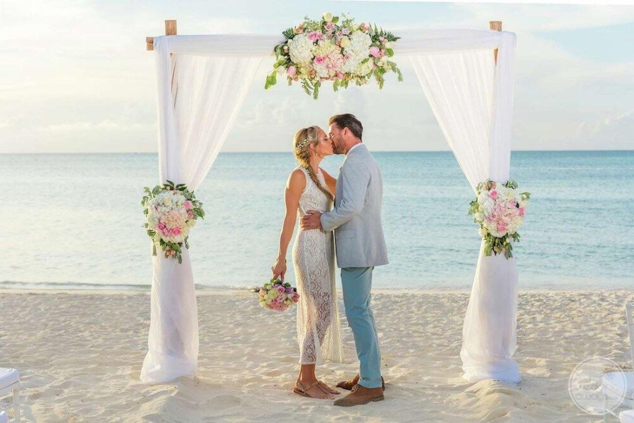 Wedding couple on the beach  exchanging of hours under a wedding gazebo