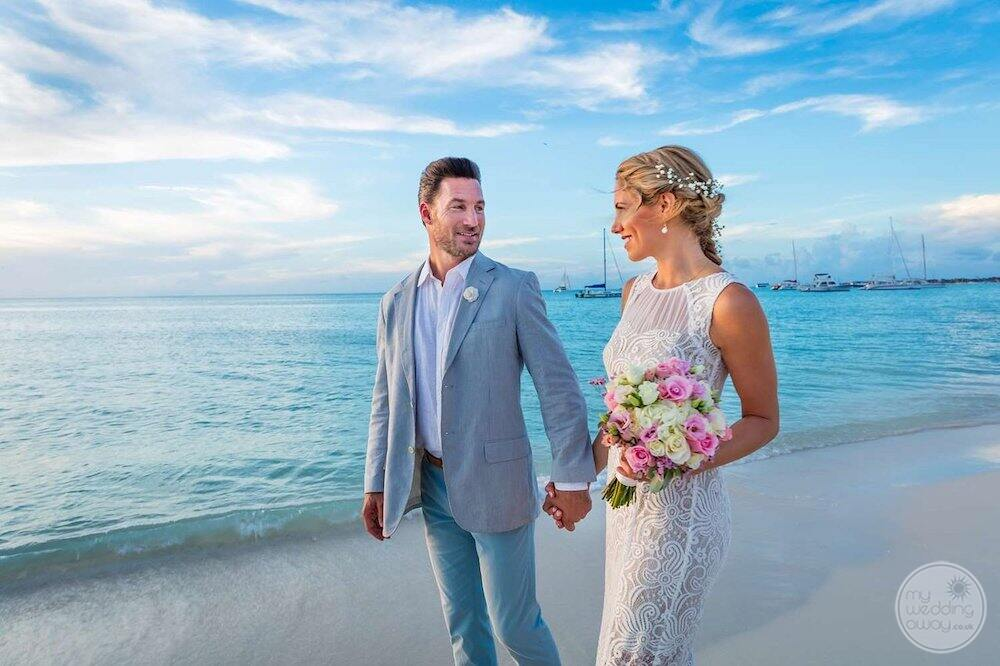 wedding couple walking hand-in-hand on the beach with boats in the background