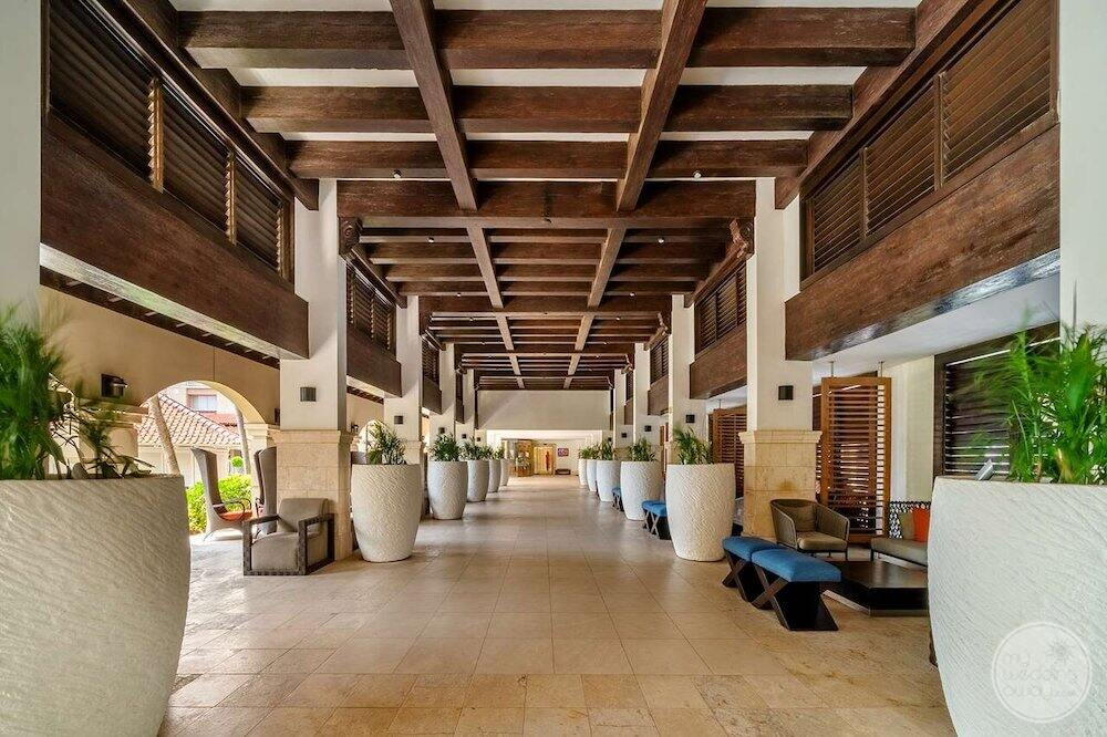 Main lobby walkway with marble floors and plants and wooden ceiling