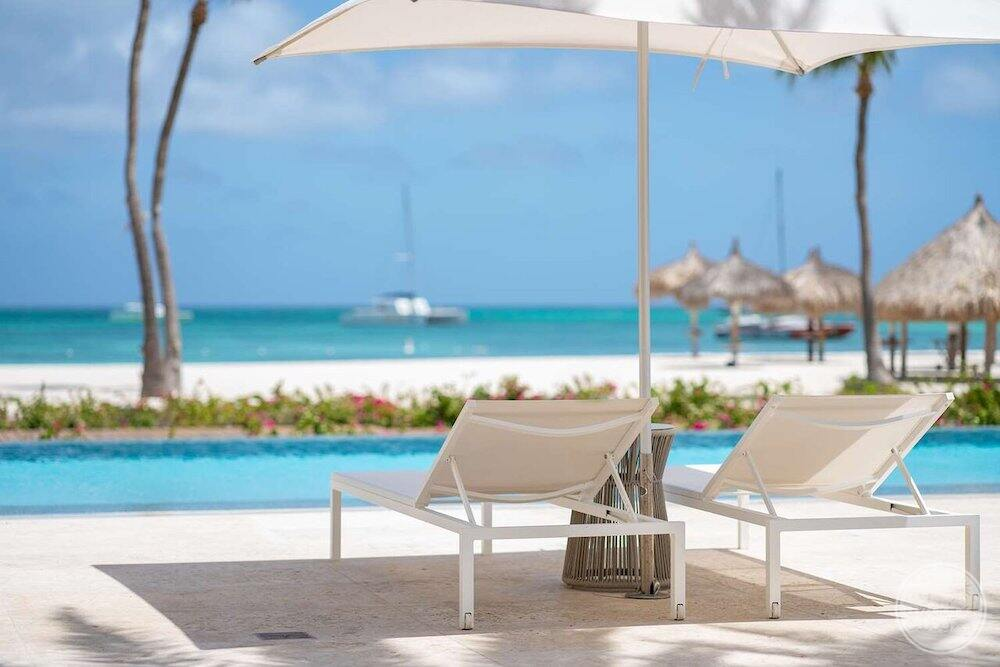 Lounge chairs and beach umbrella close to the beach by the pool