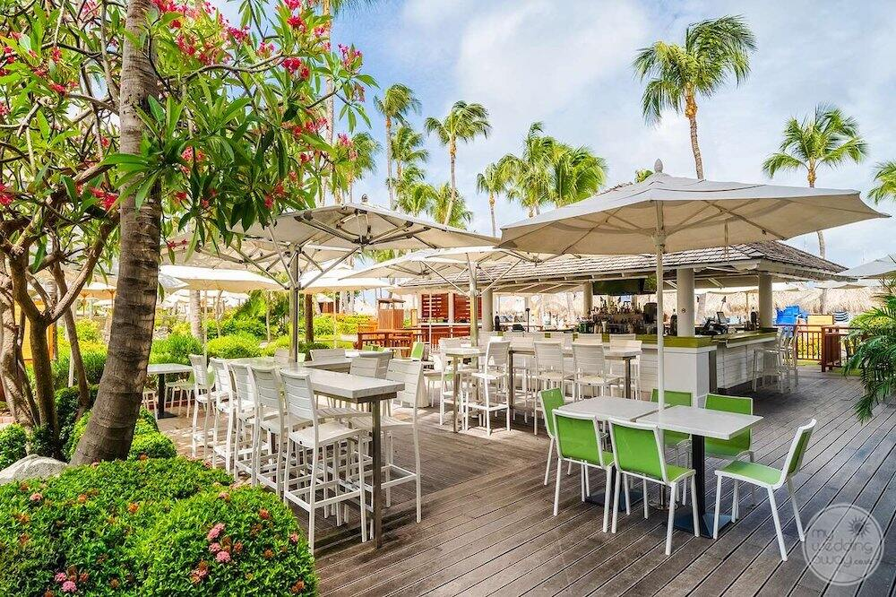 Outdoor dining area with umbrellas, bar and trees and gardens