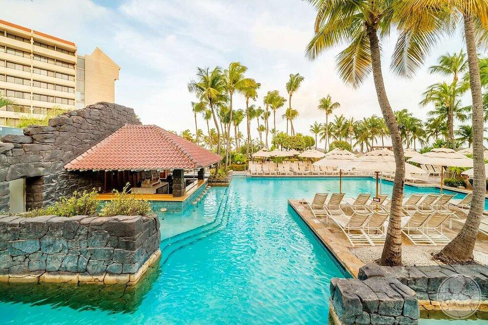 Main outdoor swimming pool with swim up bar and lounge chair is surrounded by palm trees