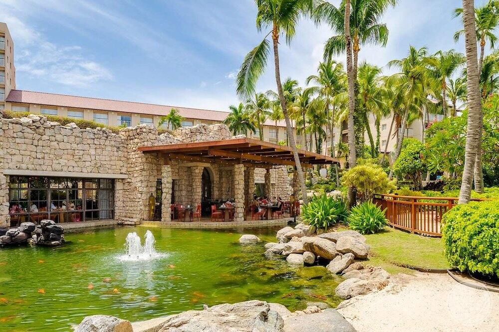 Main restaurant with surrounding ponds with koi fish and palm trees