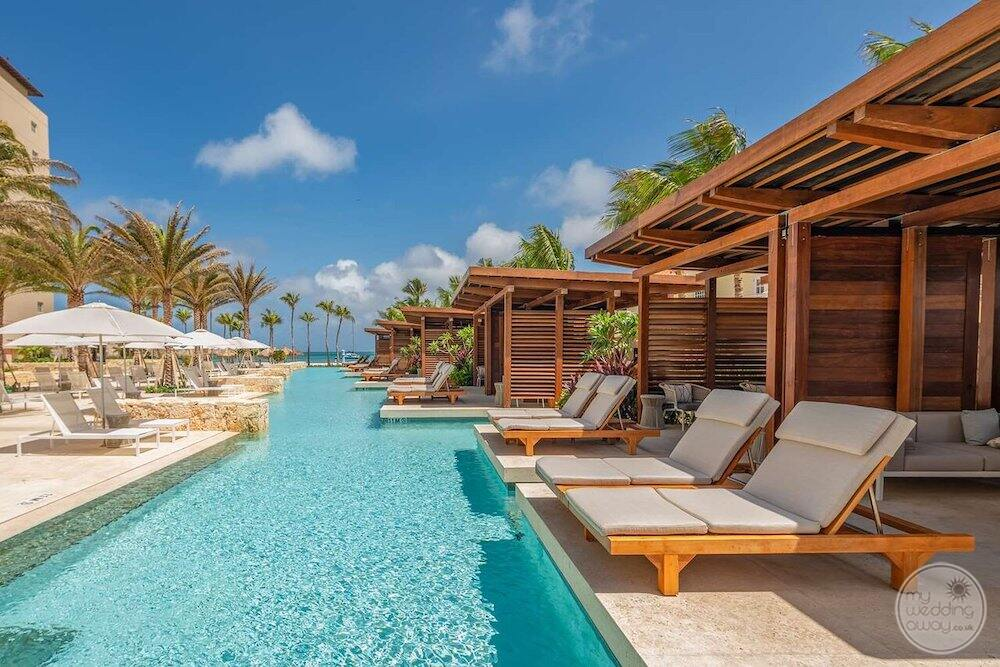 Swim up suites with plunge pool with lounge chairs palm trees and umbrellas