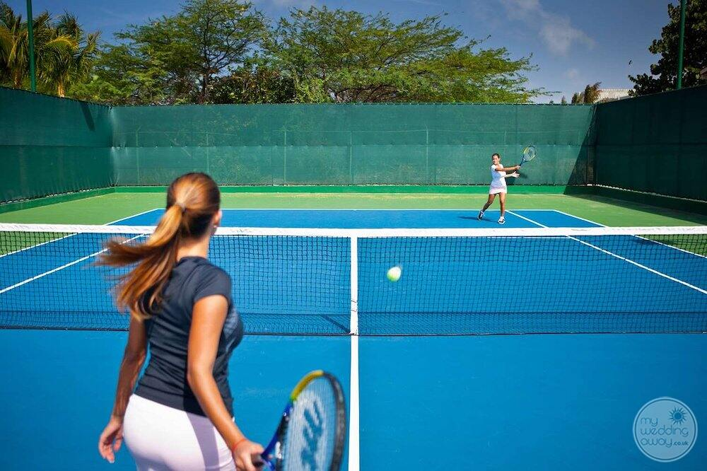 Tennis court with two guests playing tennis