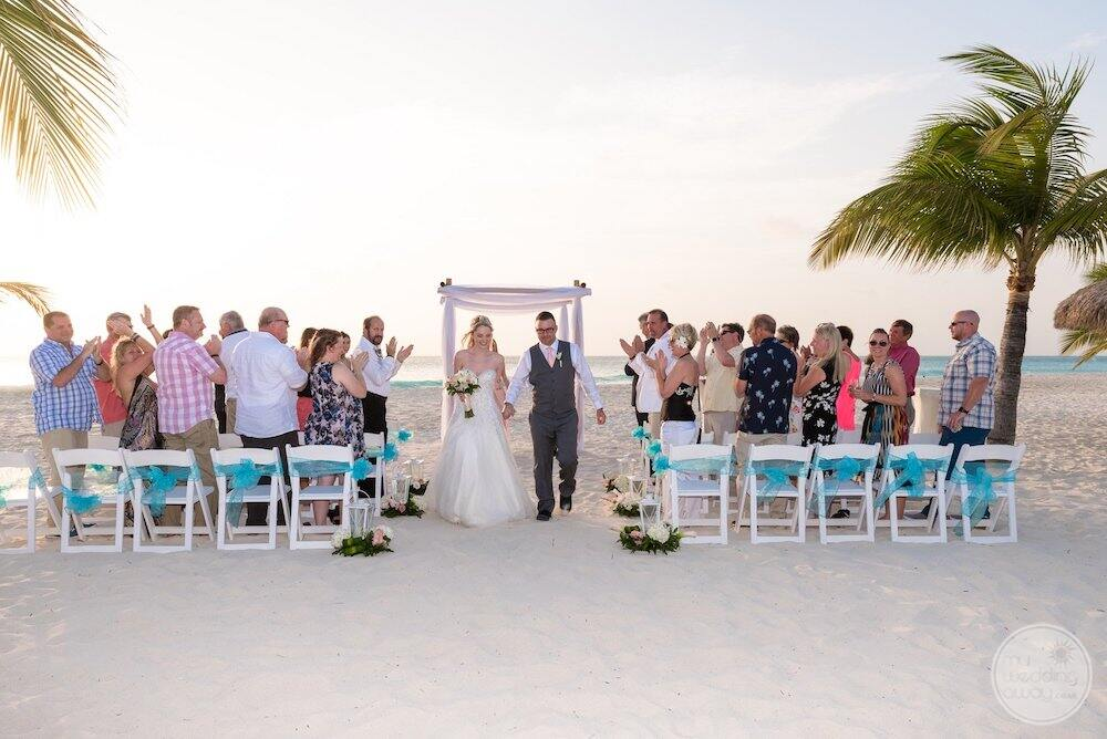 Wedding couple walking away from Sarah Moni with guests sitting on chairs on the beach