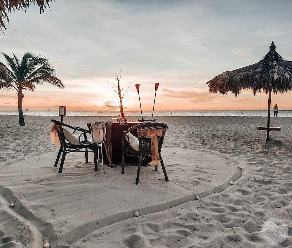 Romantic dinner set up on the beach with tables in a chair Lighting at sunset