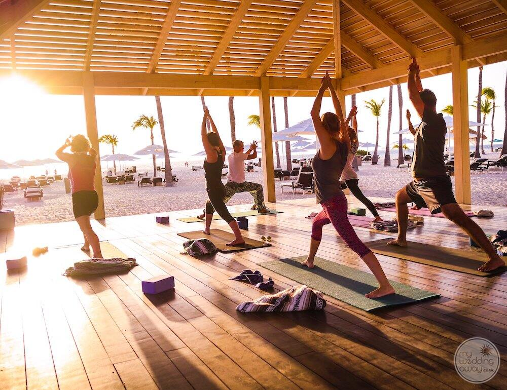 Daily yoga set up about the beach with instructor working with yoga students