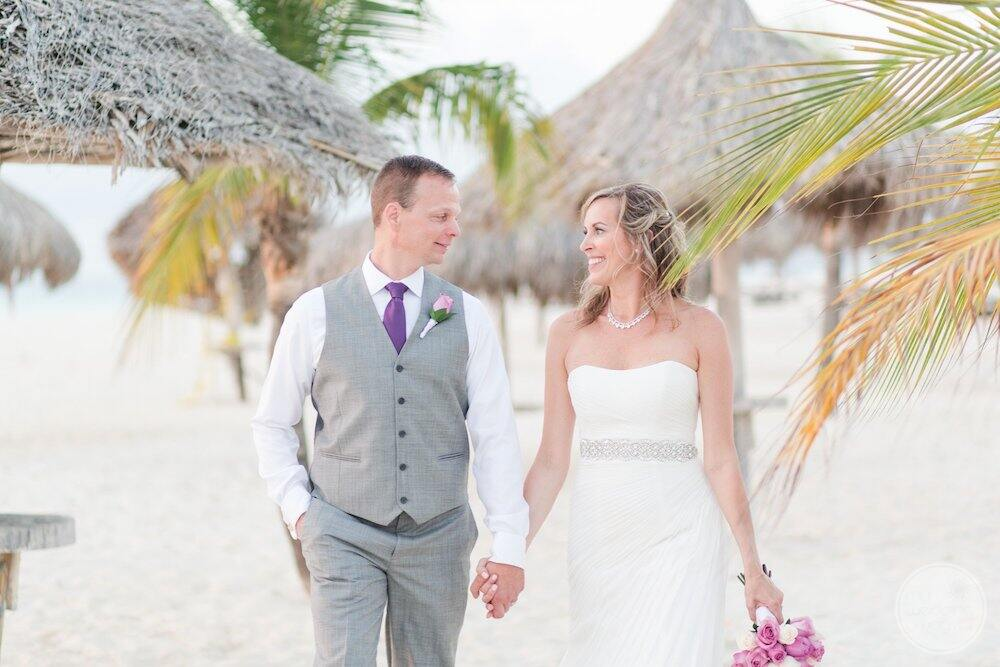 Couple holding hand-in-hand walking along the beach after the wedding