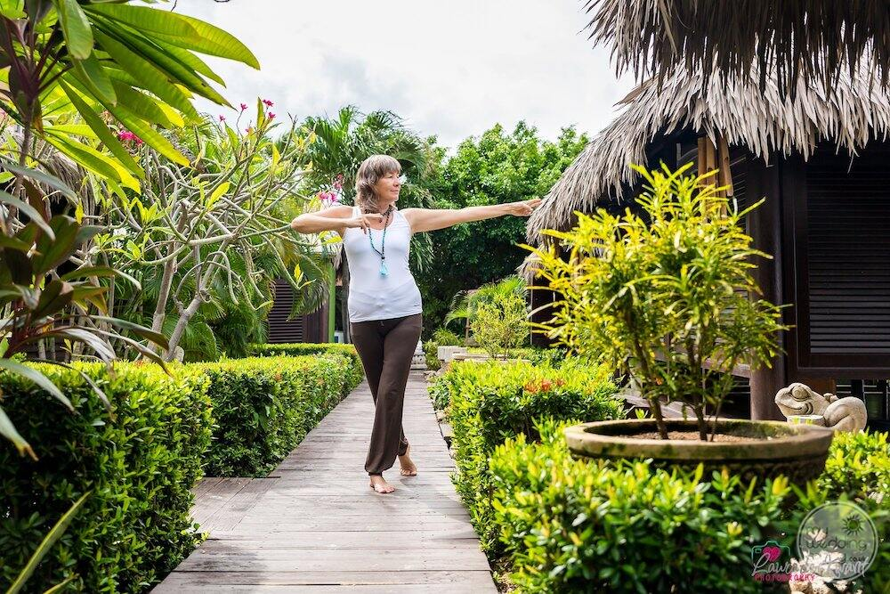 Women practising yoga on the wooden deck surrounded by greenery and plants
