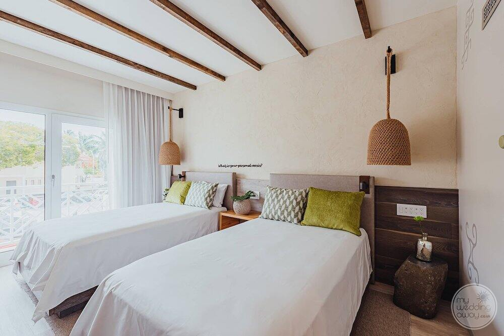 bedroom with two double beds and view of balcony overlooking the gardens