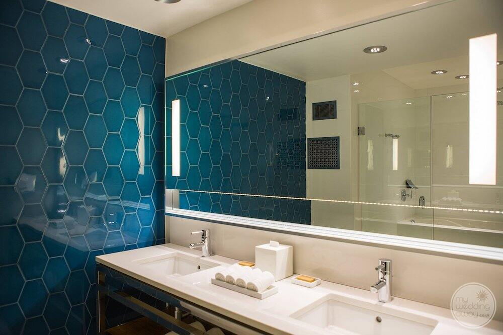 in room suite bathroom with double vanity and beautiful blue tiling