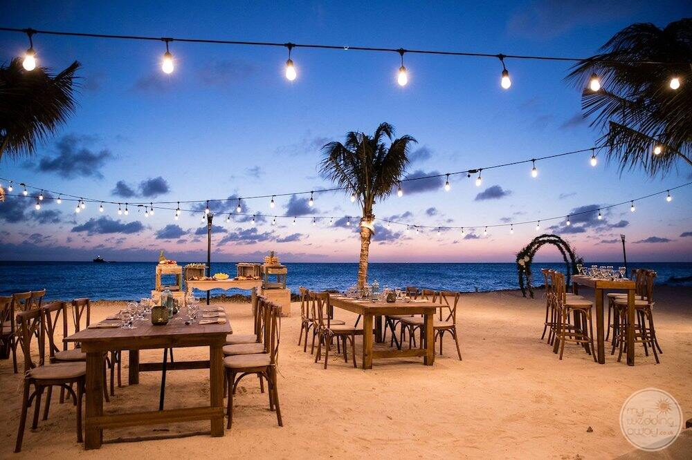 outer beach wedding reception with a beautiful wooden tables and wood chairs and soft lighting