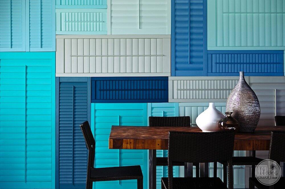 table restaurant sitting with a beautiful wood table and pattern blue and white decour on the wall