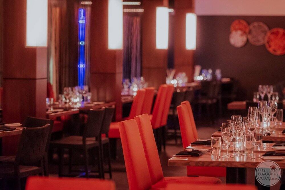 main restaurant in the evening with red chairs glassware and Lighting embiance