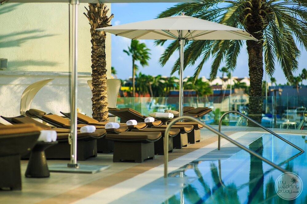 main pool area of the spa with deckchairs and umbrellas