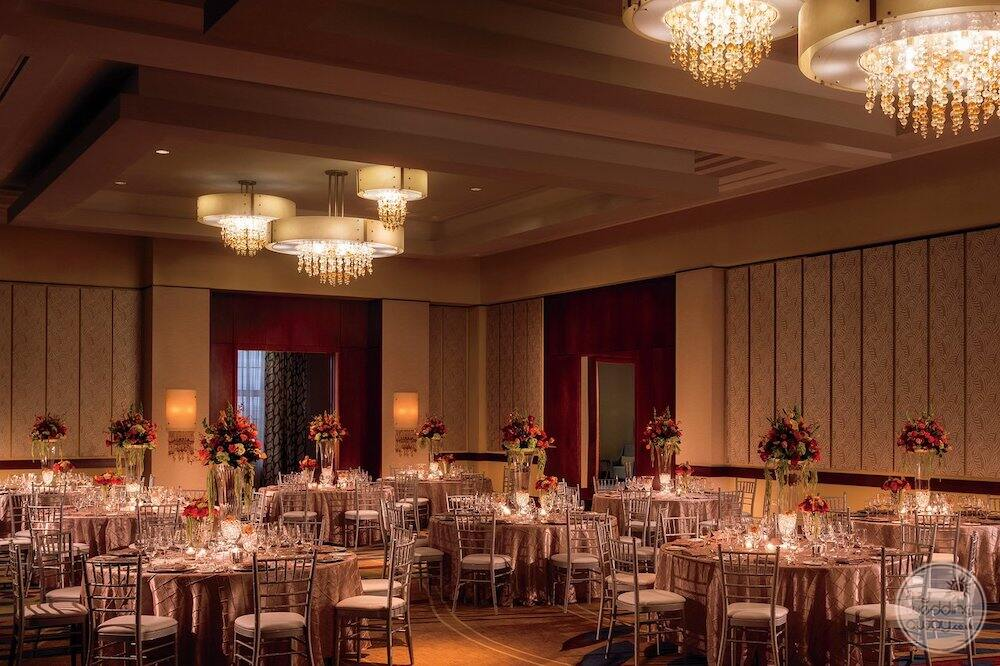 Ball room with a beautiful white chandeliers flower vases and decorative chairs