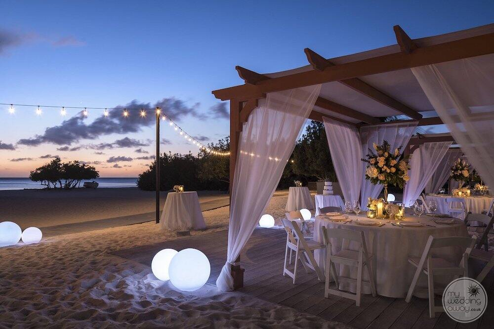 Table and chair set up on the beach for wedding reception