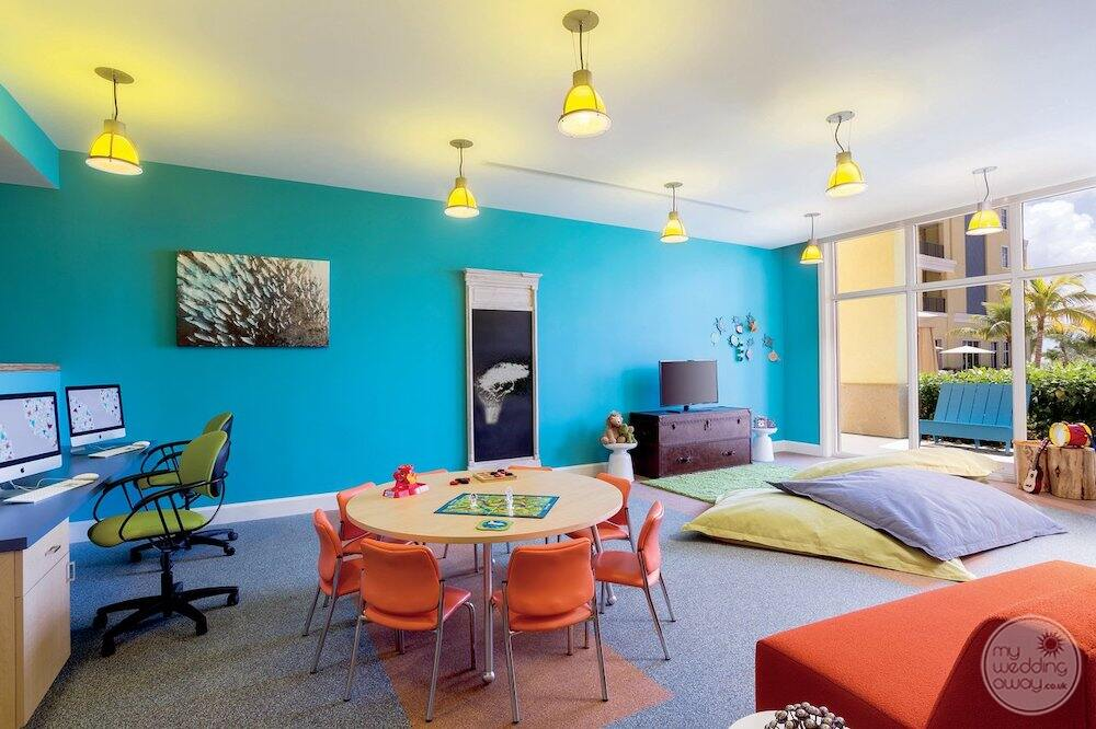 Children's play area with small table and desk chairs comfy pillows on the floor and blue walls