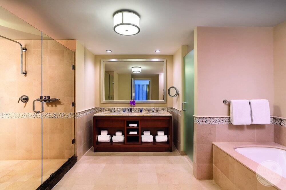 Guest bedroom bathroom with double vanity sink is in deep soaker tub