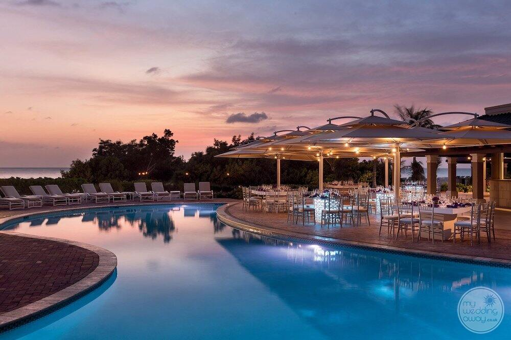 Main pool at night with lit up umbrellas tables and chairs deck for wedding reception
