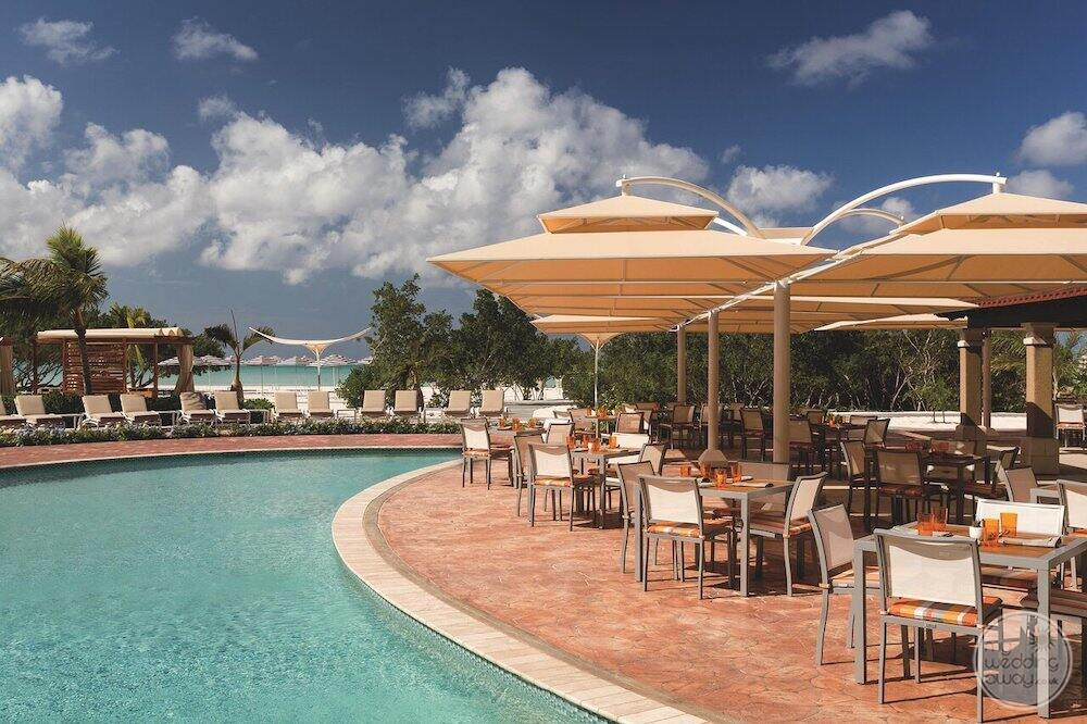 Outdoor restaurant with umbrellas close to the pool with a beach in the background