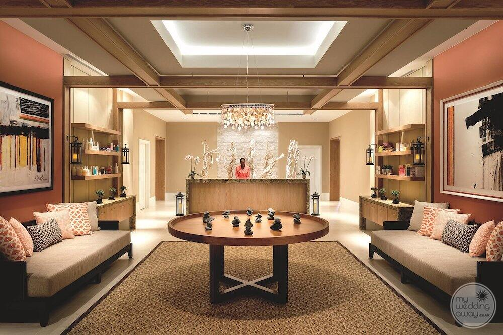 Entrance to the spa with small chandelier Long couches and table