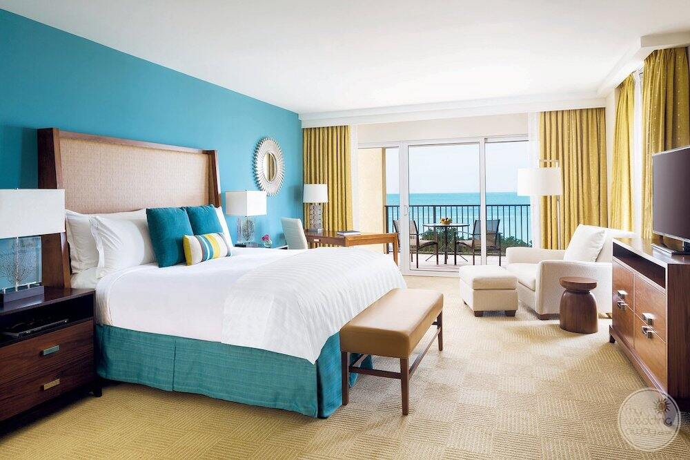 King bedroom suite with blue accents and a balcony overlooking the ocean