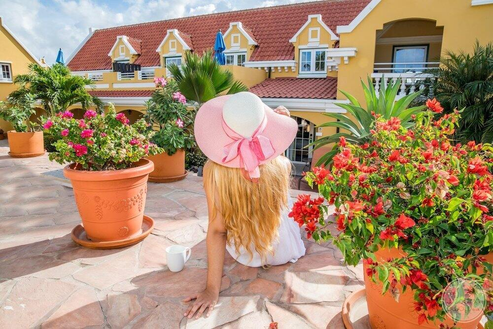guest with pink hat sitting on stone deck looking at building