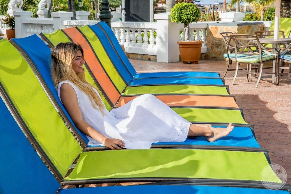 Resort guest sitting at mulit colour pool lounge chairs