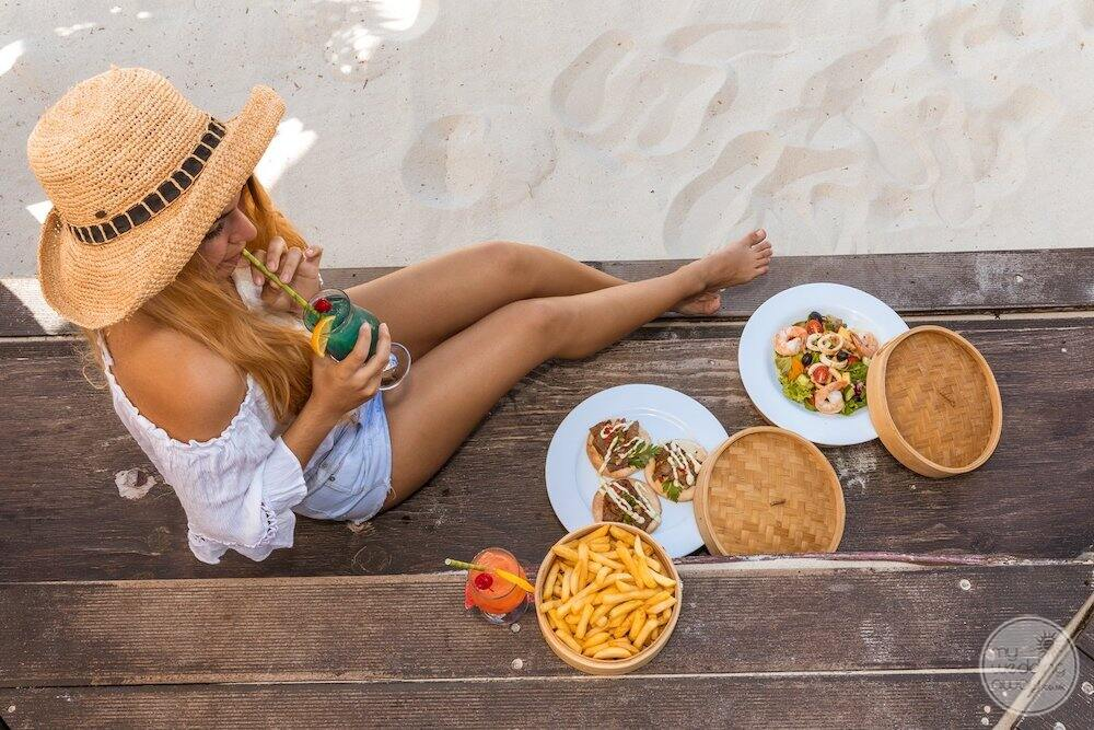 Resort guest sitting on beach drinking cocktail with plates of food beside her