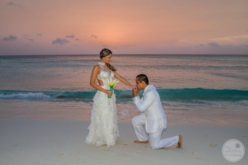 wedding couple on the beach with flower Buquet at sunset
