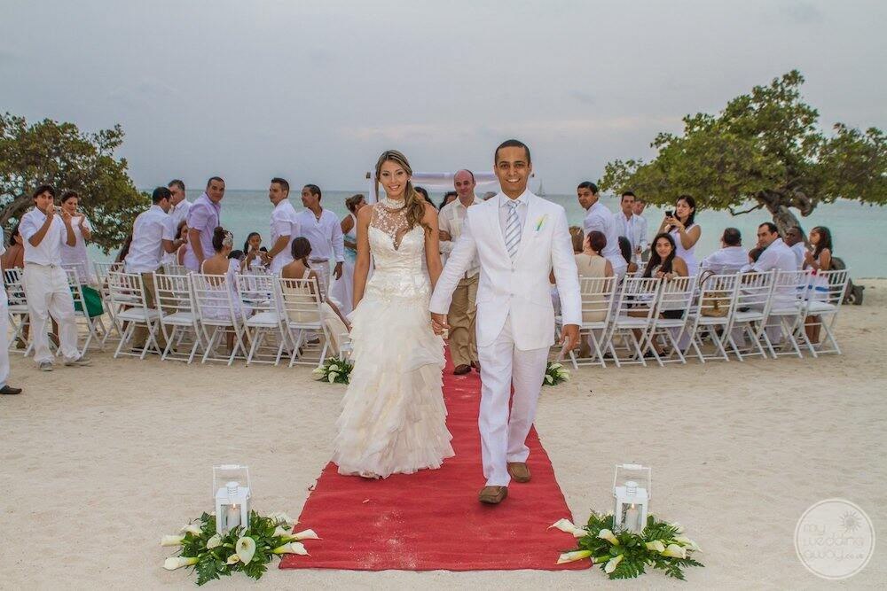 Wedding couple on the beach with ceremony guests in the background
