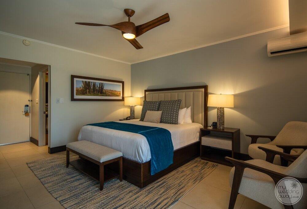 Deluxe oceanview King bedroom with lounge chair is beside the bed