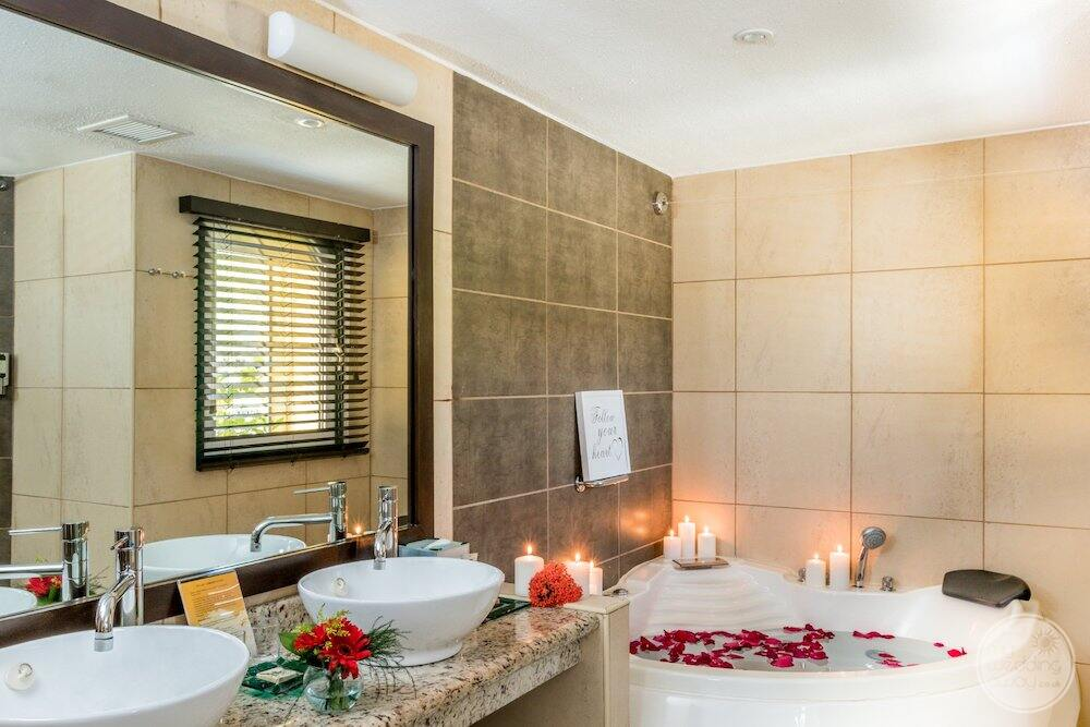 honeymoon suite with Jacuzzi and flower petals and candles and double sink vanity