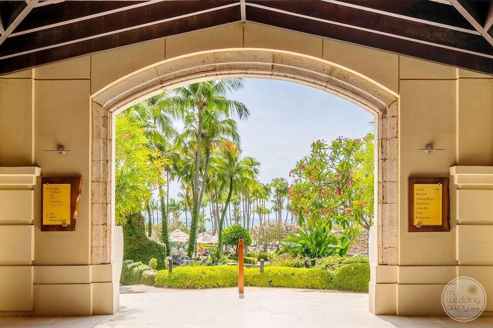 Main lobby entrance with gardens and palm trees in the background