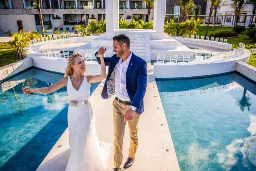 bride and groom walking away from wedding gazebo with water features beside the deck way