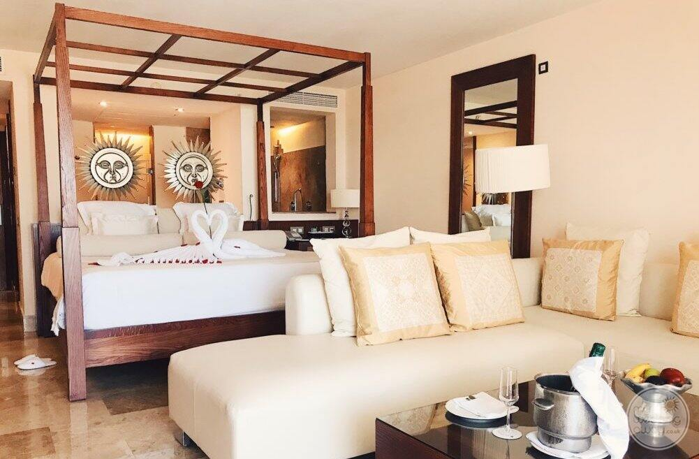 bedroom with king bed and white couch and table with champagne and fruit
