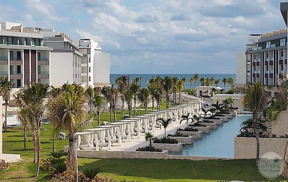 Aerial view of the main grounds with lounge chairs beside the main pool and room buildings in palm trees in the background