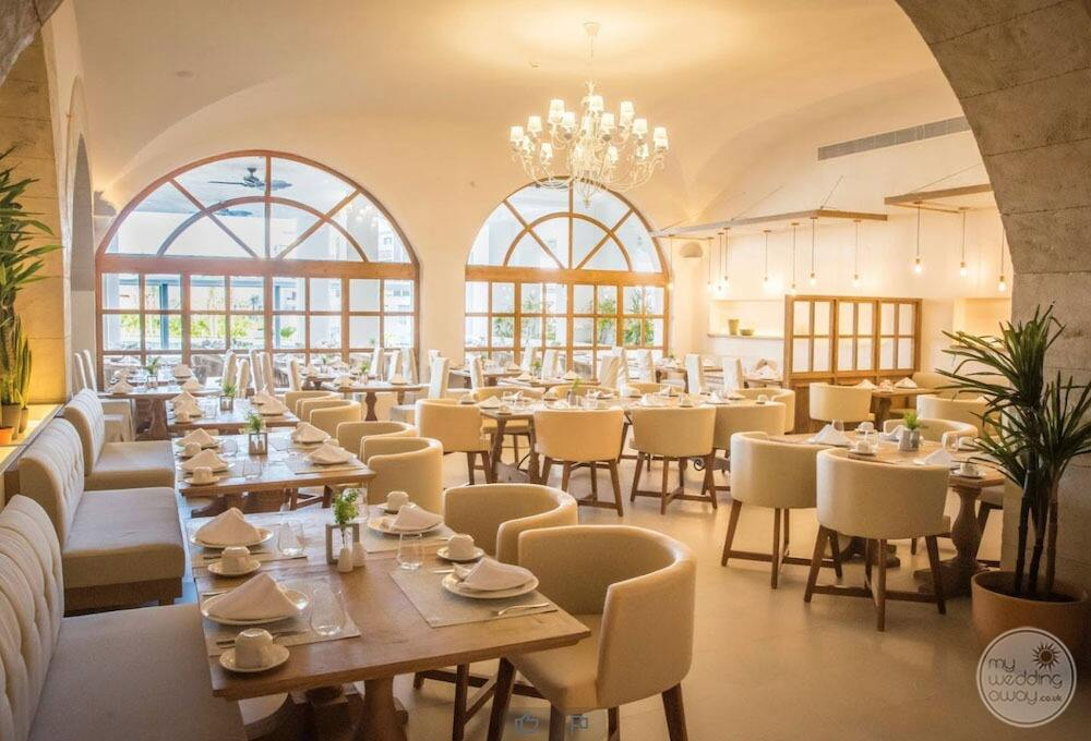 Restaurant dining room with light chair sitting Glass windows and chandelier