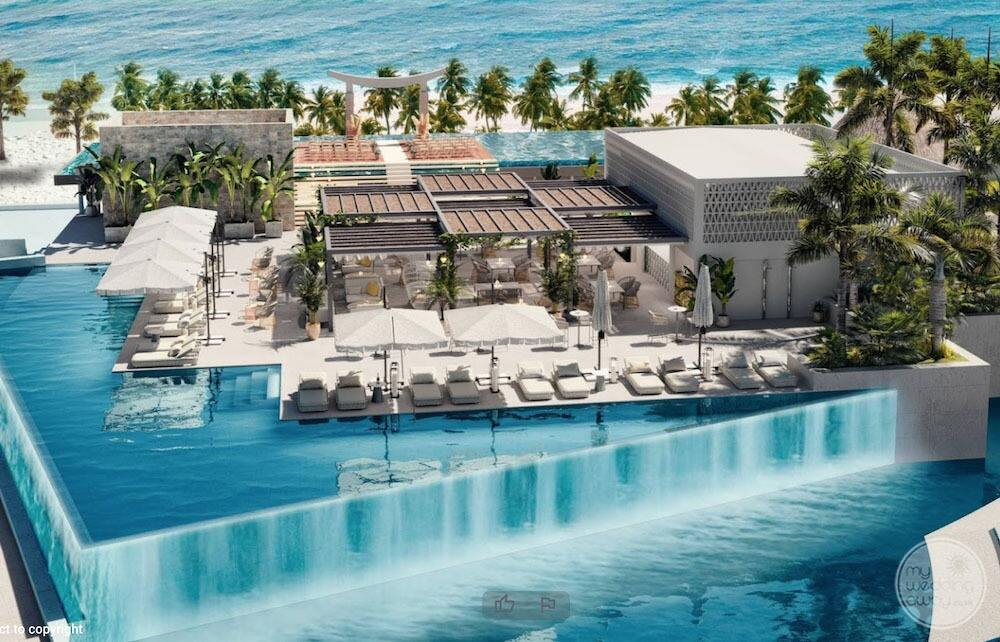 Aerial view of the main pool with infinity citing lounge chairs and restaurant and ocean in the background