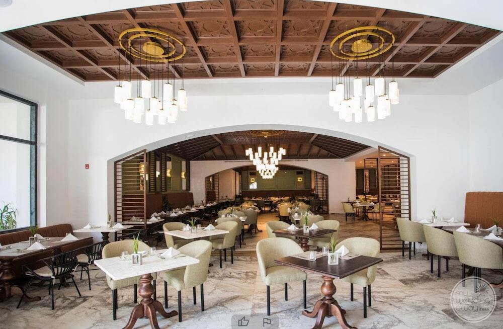 Main restaurant with banquet seating and white chandeliers